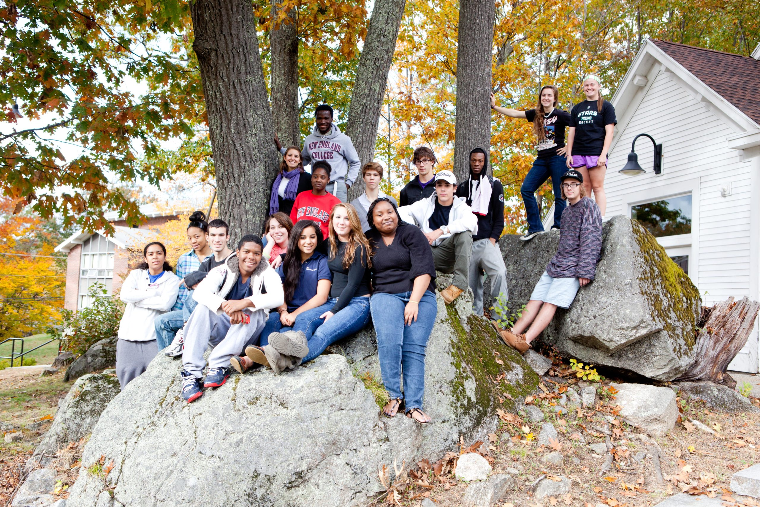 New students sit on a large rock on NEC's Henniker campus