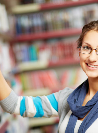 Female student selects a book in a library